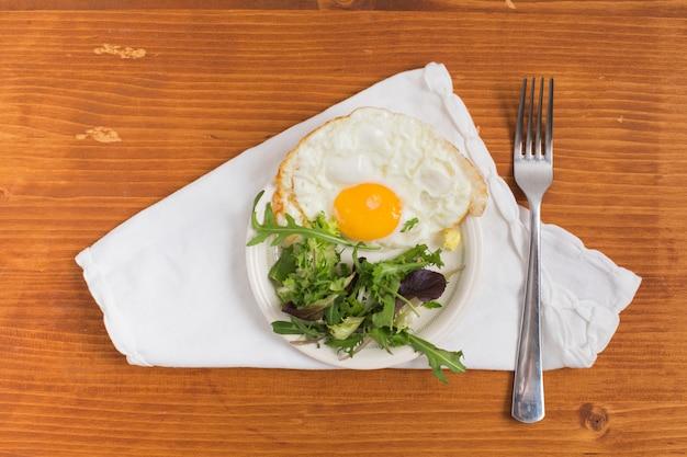 Meio ovo frito com salada no prato e garfo sobre o guardanapo branco contra o pano de fundo texturizado de madeira Foto gratuita