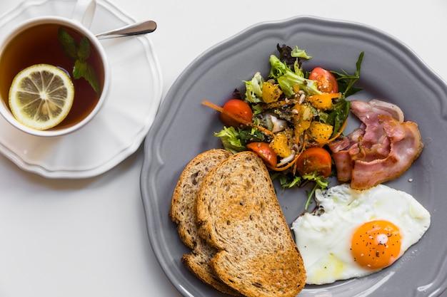 Meio ovo frito; torrada; salada; bacon na placa cinza com limão e hortelã xícara de chá no fundo branco Foto gratuita