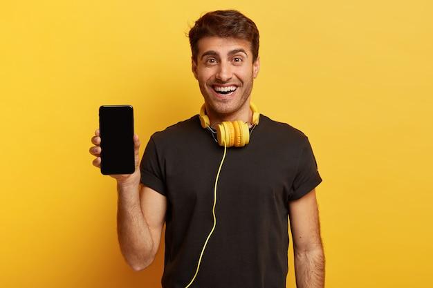 Meio plano de homem otimista segurando smartphone com tela de simulação Foto gratuita