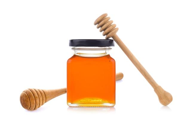 Mel com mel de madeira dipper na jarra Foto Premium