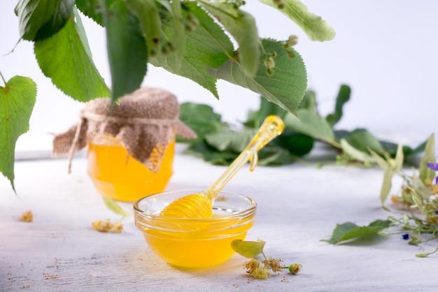 Mel de tília em pote e tigela com uma concha de mel em uma mesa de madeira branca Foto Premium