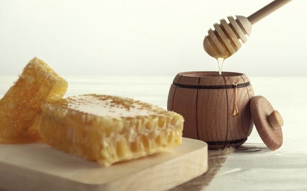 Mel dipper em pote de madeira e pente de mel na bandeja de madeira Foto Premium