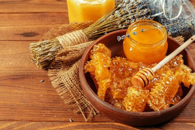 Mel em pote com dipper mel no vintage de madeira Foto Premium
