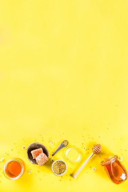 Mel floral orgânico, em frascos, com pentes de pólen e mel, com flores silvestres layout criativo fundo amarelo brilhante vista superior espaço de cópia Foto Premium