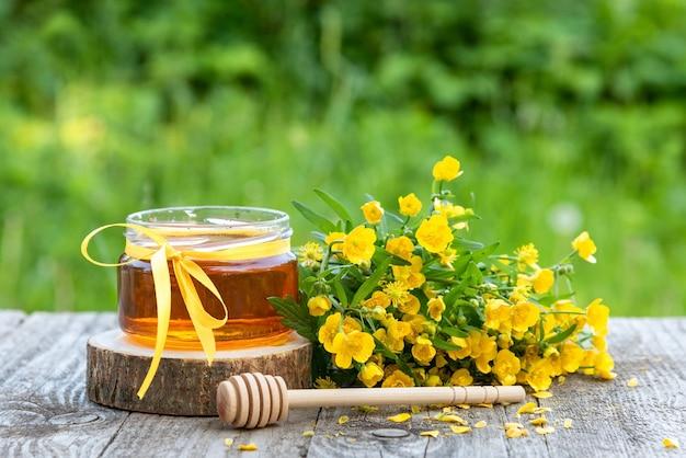 Mel fresco em uma jarra e flores amarelas. Foto Premium