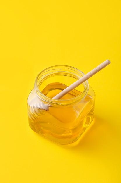 Mel líquido da flor no frasco de vidro com a colher de madeira do mel. Foto Premium
