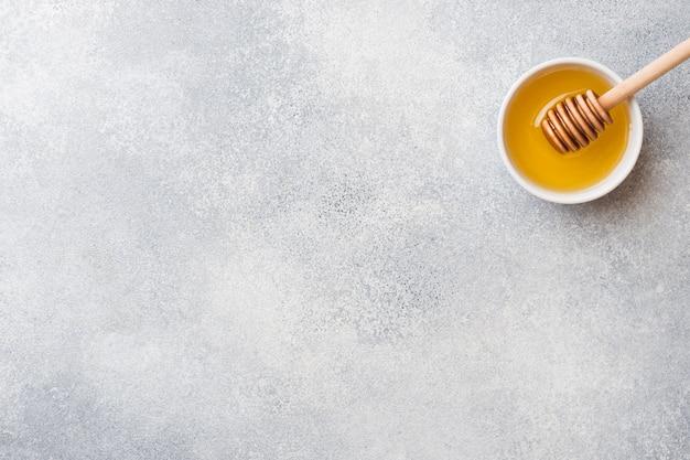 Mel líquido e palito de mel em um Foto Premium