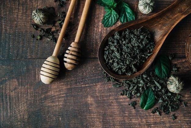 Mel vara e colher com ervas de chá Foto gratuita