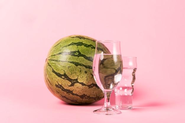 Melancia de tamanho completo e copos com água Foto gratuita