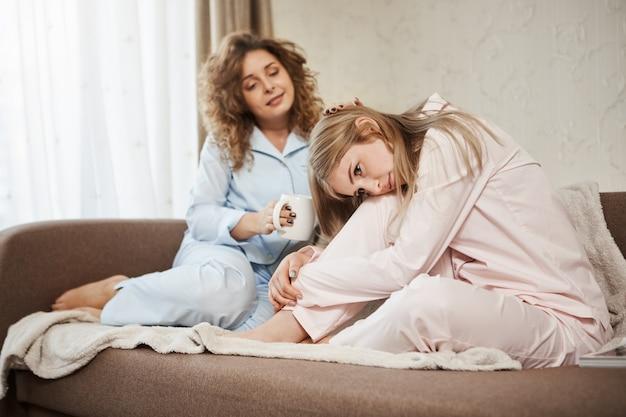 Melhor amiga animar loira de coração partido. retrato de duas mulheres atraentes, sentado no sofá em roupas de noite. menina de cabelos encaracolados tomando café, dando tapinhas na cabeça da irmã enquanto ela está chateada ou sentindo cólicas Foto gratuita
