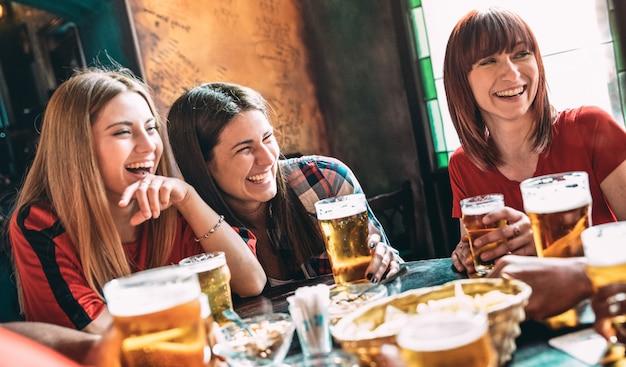 Melhores amigas felizes bebendo cerveja no bar Foto Premium