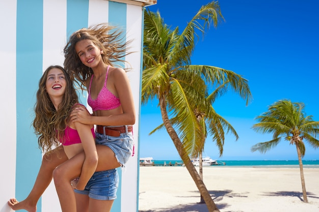 Melhores amigas meninas nas costas na praia de verão Foto Premium