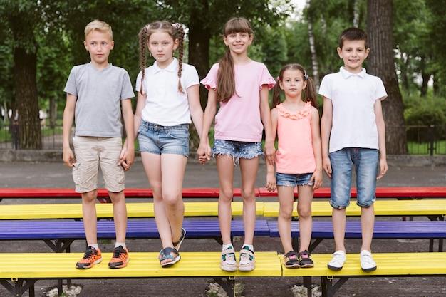 Melhores amigas, posando no banco colorido Foto gratuita