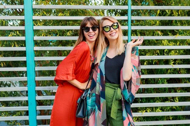 Melhores amigas se divertindo juntos e curtindo férias na ensolarada cidade moderna Foto gratuita