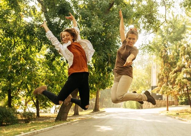 Melhores amigos pulando ao ar livre Foto gratuita