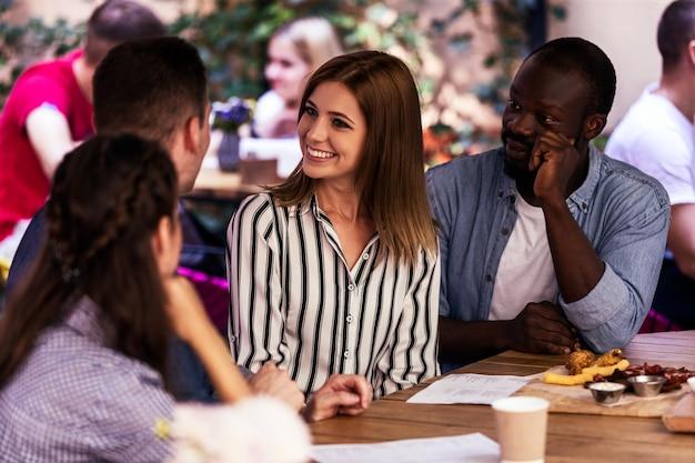 Melhores amigos sentados ao redor da mesa no terraço de um café tranquilo e aconchegante Foto gratuita