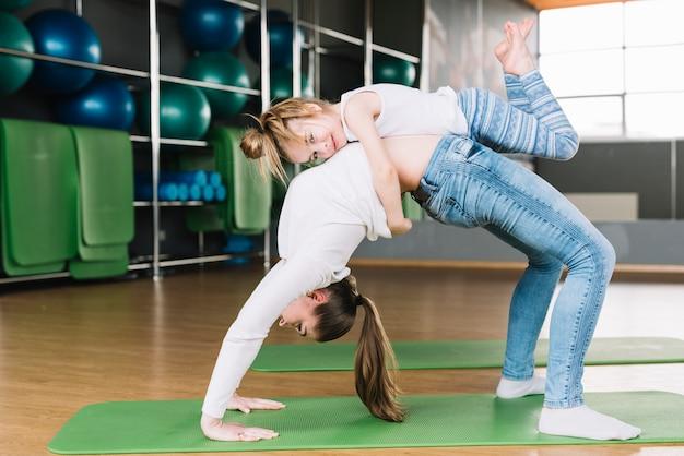 Menina, abraçando, dela, mãe, exercício, ligado, exercício verde, tapete Foto gratuita