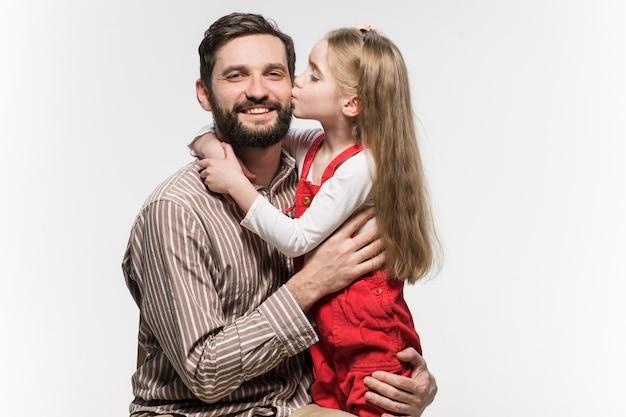 Menina abraçando o pai dela sobre uma parede branca Foto gratuita