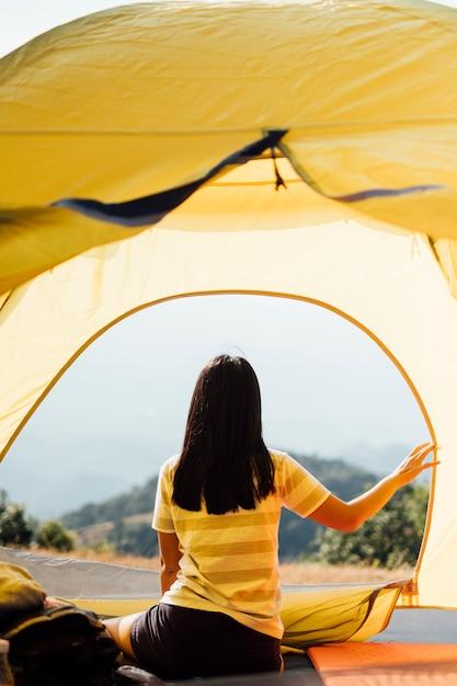 Menina acorda de manhã na tenda e vista para a montanha na tailândia Foto gratuita