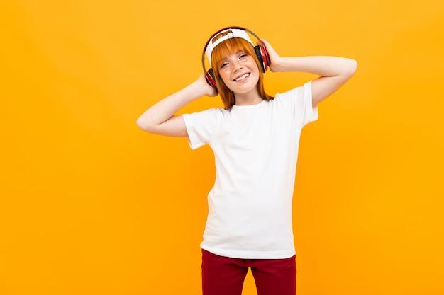 Menina adolescente bonita de aparência europeia em um amarelo isolado em uma camiseta branca ouve música em fones de ouvido Foto Premium