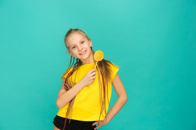 Menina adolescente com pirulito colorido em um azul Foto gratuita
