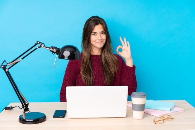 Menina adolescente com um laptop em uma mesa, mostrando um sinal de ok com os dedos Foto Premium