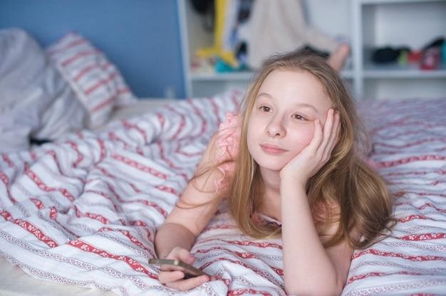 Menina adolescente, encontrar-se cama, com, telefone Foto Premium