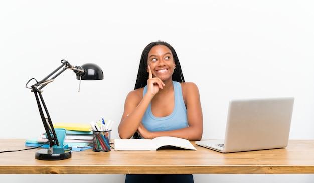 Menina adolescente estudante pensando uma idéia enquanto olhando para cima Foto Premium