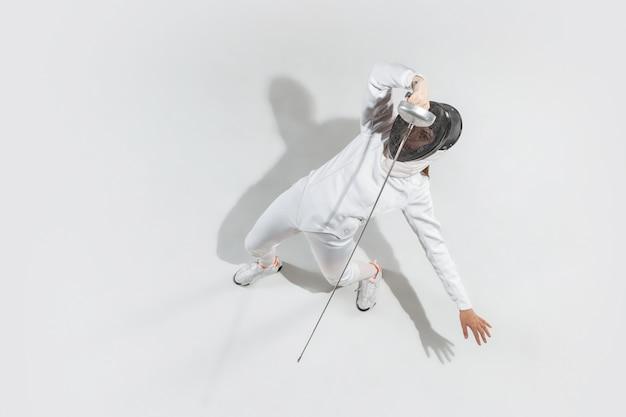 Menina adolescente fantasiada de esgrima com a espada na mão, isolada no fundo branco, vista superior Foto gratuita