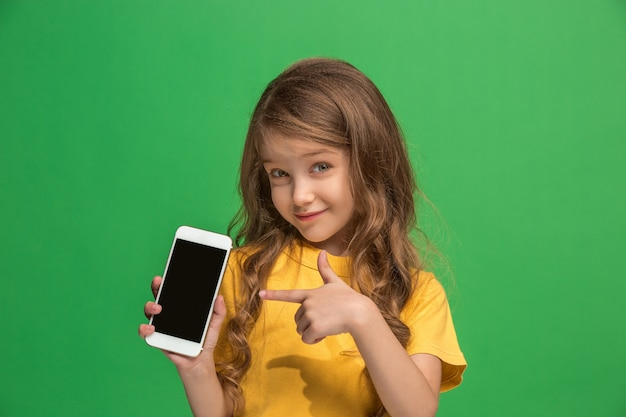 Menina adolescente feliz em pé, sorrindo com o celular em um verde moderno. belo retrato feminino de meio corpo Foto gratuita