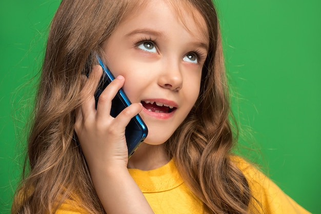 Menina adolescente feliz em pé, sorrindo com o celular sobre o moderno estúdio verde. Foto gratuita