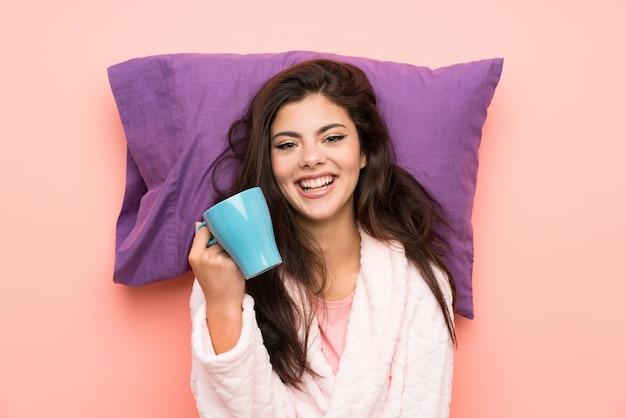 Menina adolescente feliz em roupão sobre backgrounnd rosa e segurando uma xícara de café Foto Premium