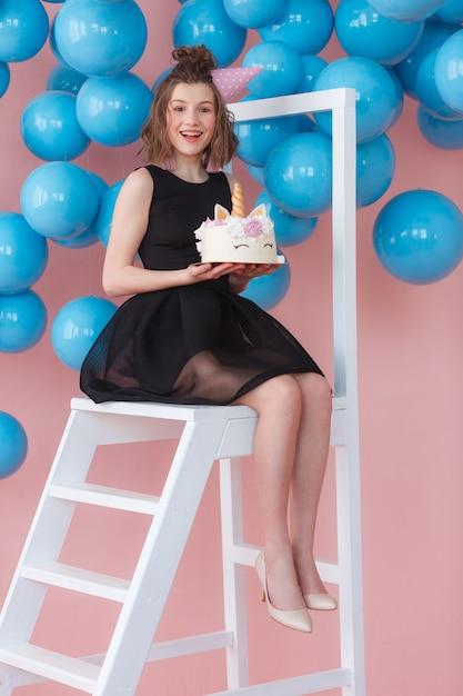 Menina adolescente feliz que mantém o bolo mergulhado do unicórnio decorado com merengues. Foto gratuita