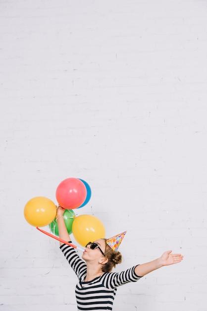 Menina adolescente, ficar, contra, branca, parede tijolo, soprando, partido, chifre Foto gratuita