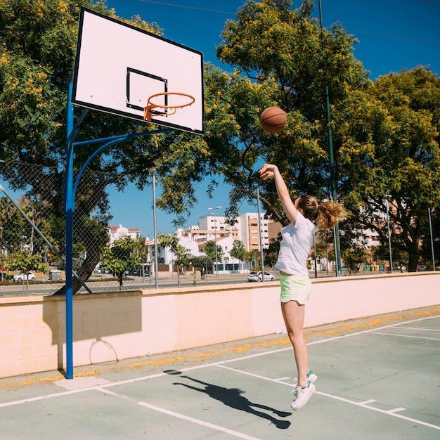Menina adolescente jogando basquete no campo Foto gratuita