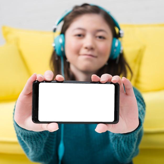 Menina adolescente, mostrando, smartphone Foto gratuita