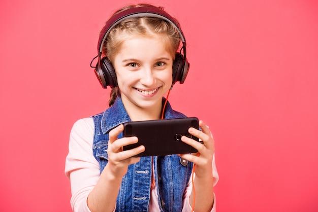 Menina adolescente, ouvindo música em fones de ouvido e segurando smartphon Foto Premium