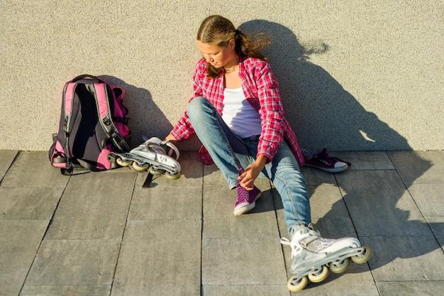 Menina adolescente remove tênis e roupas de patins Foto Premium