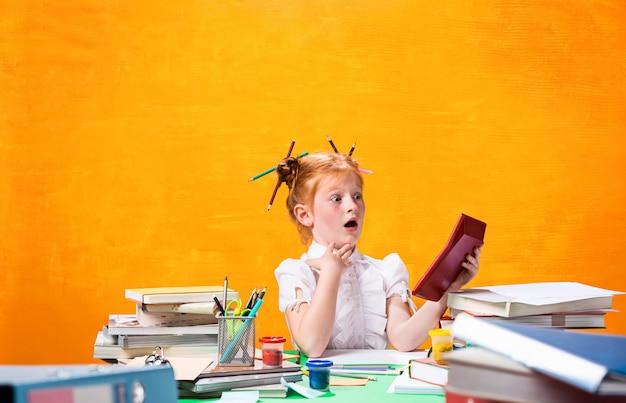 Menina adolescente ruiva com muitos livros em casa Foto gratuita