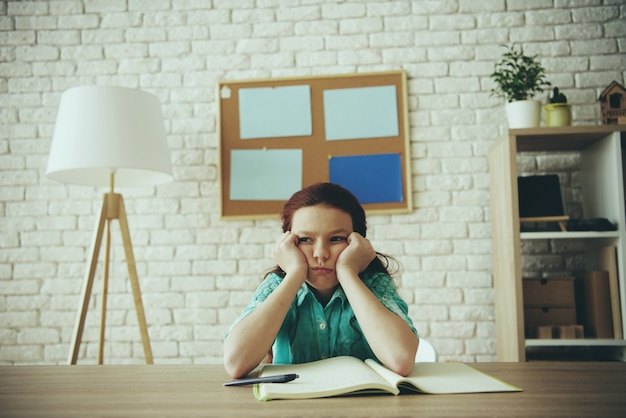 Menina adolescente ruiva está entediada enquanto fazendo lição de casa. Foto Premium
