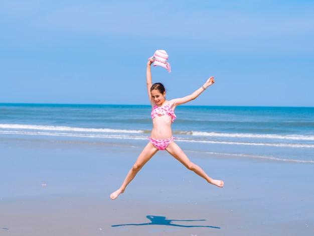 Menina adolescente se divertindo na praia tropical e saltar para o ar na costa do mar Foto Premium