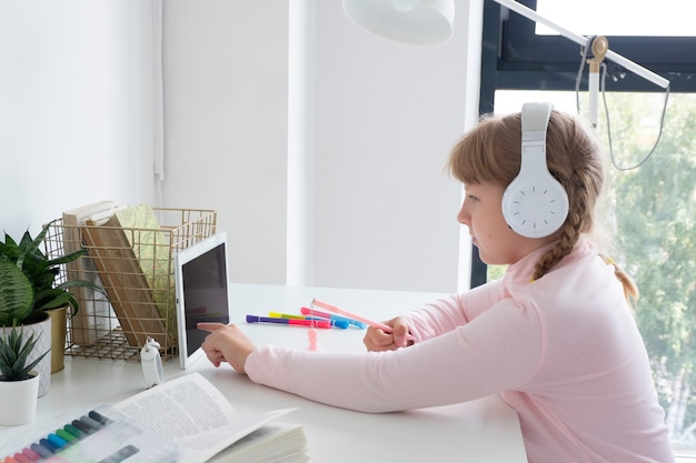 Menina adolescente se senta à mesa com um tablet e em fones de ouvido e escreve em um caderno. conceito de ensino à distância. Foto Premium