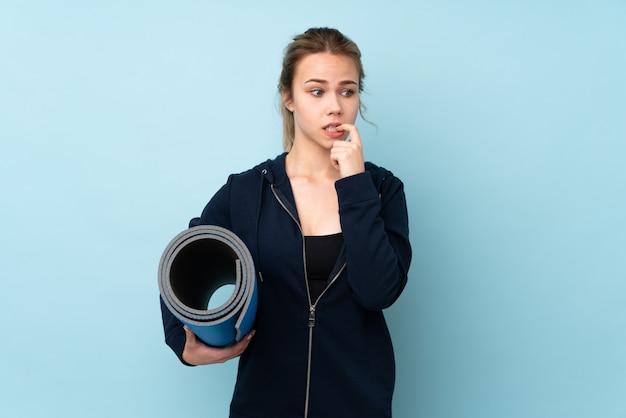 Menina adolescente segurando o tapete na parede azul, nervoso e assustado Foto Premium