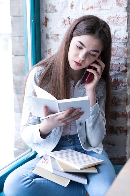 Menina adolescente sentado com o livro aberto e falando no celular Foto gratuita