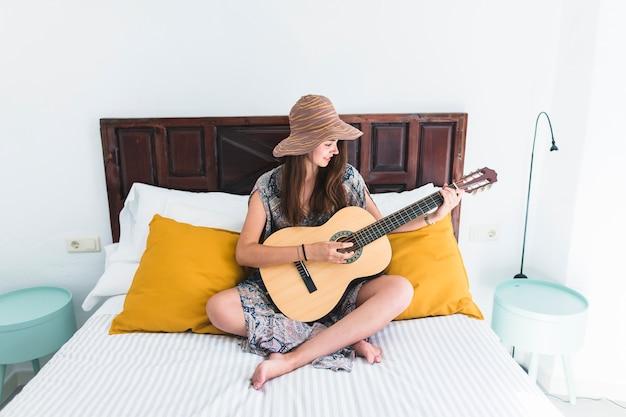 Menina adolescente, sentar-se cama, violão jogo Foto gratuita