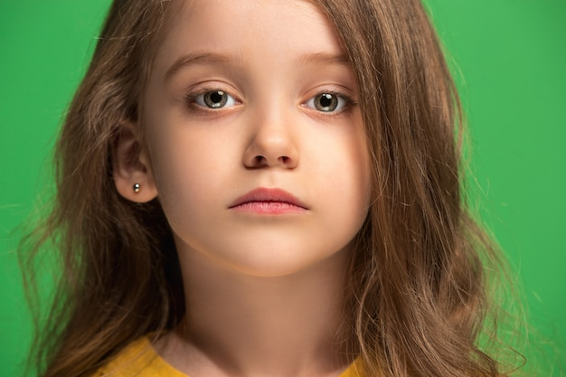 Menina adolescente séria, triste, duvidosa e pensativa em pé no estúdio verde Foto gratuita