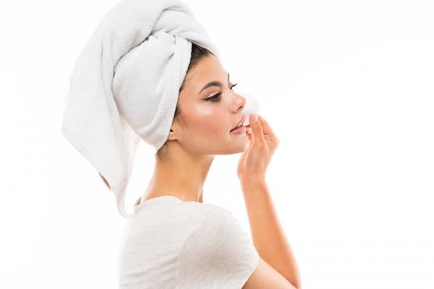 Menina adolescente sobre maquiagem de wallremoving branco isolado do rosto com almofada de algodão Foto Premium