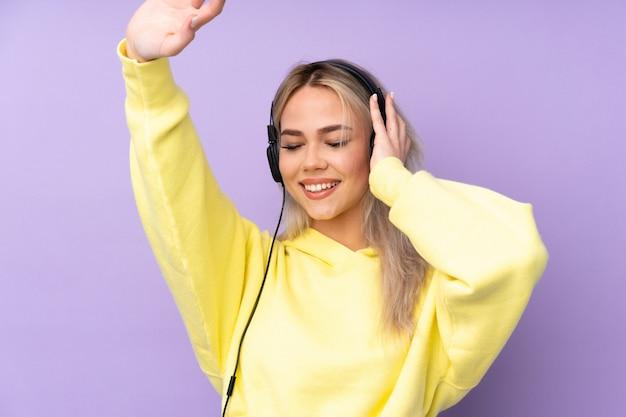 Menina adolescente sobre música roxa isolada parede e dança Foto Premium