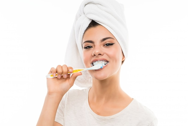 Menina adolescente sobre parede branca isolada, escovando os dentes Foto Premium