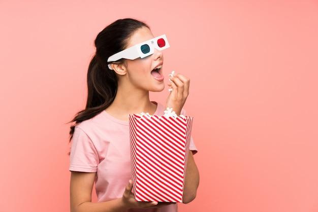 Menina adolescente sobre parede rosa isolada, comendo pipocas com óculos 3d Foto Premium